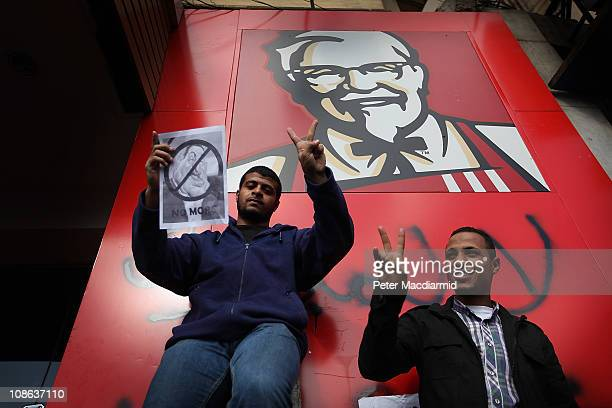 Protestors gesture as they stand next to a Kentucky Fried Chicken restaurant on January 31 2011 in Cairo Egypt As President Mubarak struggles to...