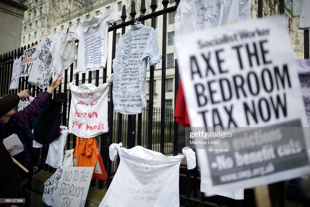 Protestors hang signs on the gates as they demonstrate against the proposed 'bedroom tax' gather in Trafalgar Square before marching to Downing Street on March 30, 2013 in London, England. Welfare groups are protesting the government's plans to cut benefits where families have surpassed the number of rooms they require.