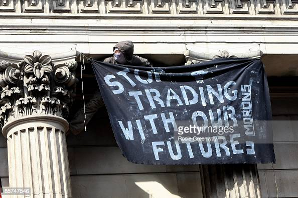 A protestors hangs a banner during G20 demonstrations outside the Bank of England on April 1 2009 in London England Protesters marched through London...