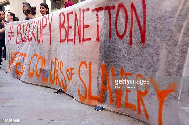 Protestors hold a banner painted with the slogan 'Blockupy Benetton United Colors of Slavery' outside Benetton's flagship store on May 23 2013 in...