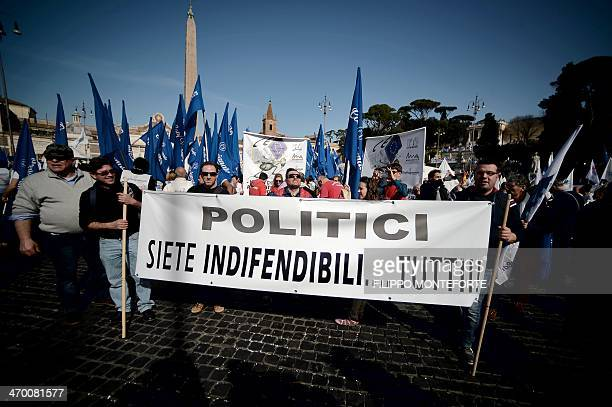 Protestors hold a banner reading 'politicians you are all indefensible' during a demonstration in downtown Rome's Piazza del Popolo on February 18...