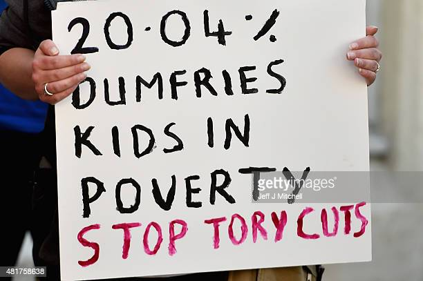 Protestors hold a demonstration as Scotland's only Conservative MP David Mundell opens a foodbank at the Apex Centre to help people struggling with...