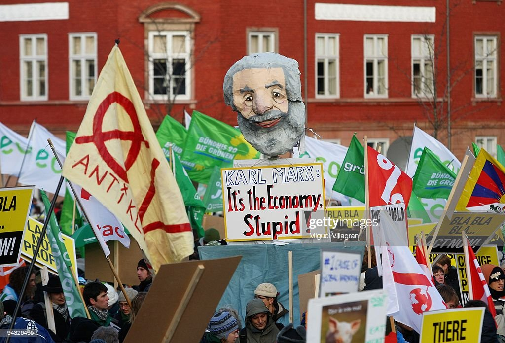Protestors hold a figure depicting Karl Marx with the writing ''It's the economy stupid' as they march towards the United Nations Climate Change...