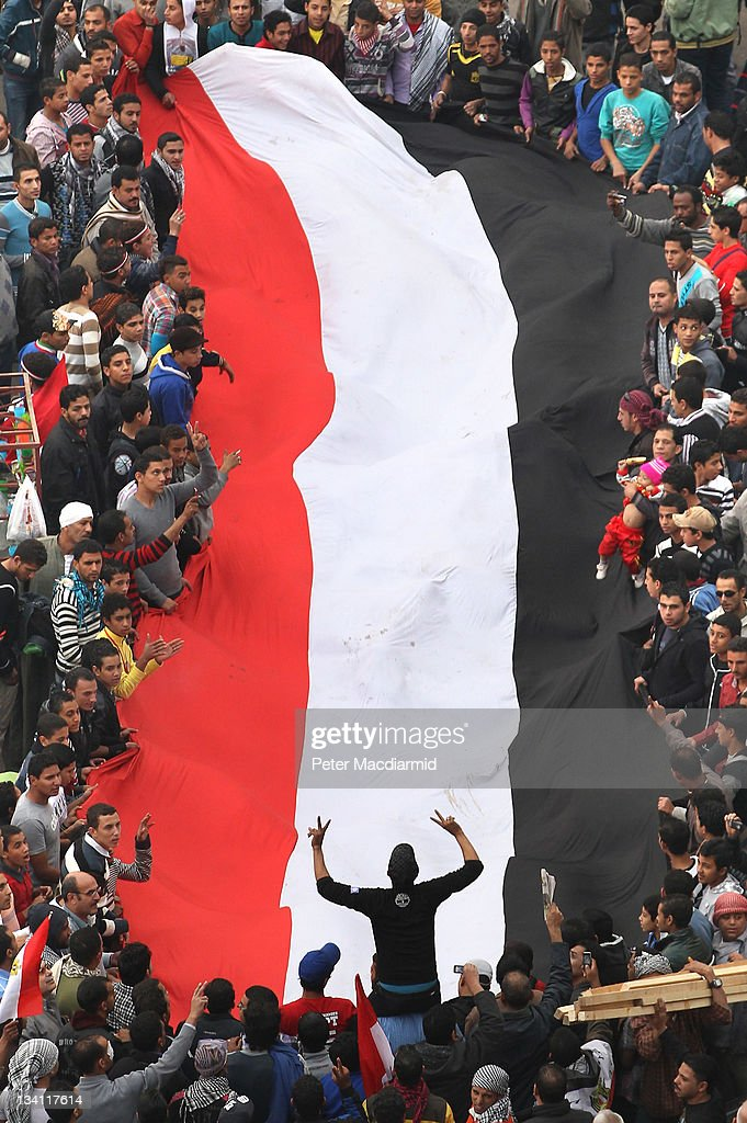 Protestors hold a giant Egyptian flag aloft in Tahrir Square on November 26, 2011 in Cairo, Egypt. Thousands of Egyptians are continuing to occupy Tahrir Square ahead of parliamentary elections to be held on November 28.