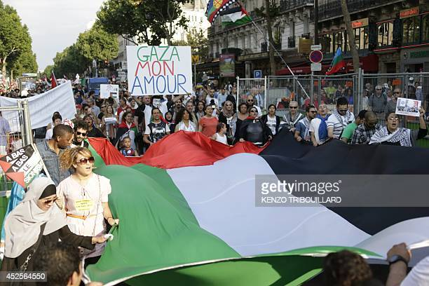 Protestors hold a Palestinian flag and a placard reading 'Gaza My Love' as they take part in a demonstration on July 23 2014 in Paris to denounce...