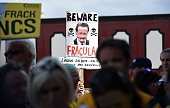 Protestors hold a placard depicting British Prime Minister David Cameron as 'Fracula' as they demonstrate outside Lancashire County Hall in Preston...