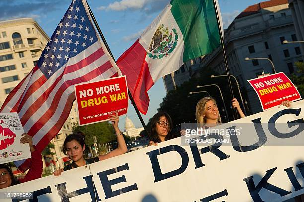 Protestors hold a sign along with a US and Mexican flag in front of the US Capitol in Washington on September 10 2012 during the 'Caravan for Peace'...