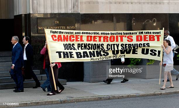 Protestors hold a sign in front of the Theodore Levin US Courthouse in Detroit Michigan US on Wednesday July 24 2013 Detroit began its first court...