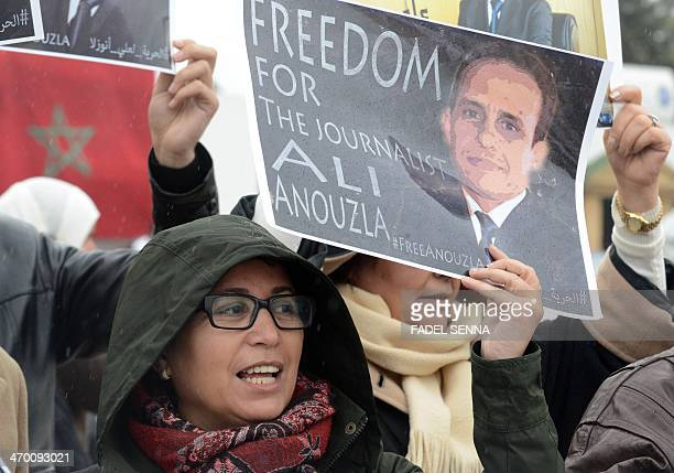 Protestors hold banners in support of Ali Anouzla head of the Arabic version of independent news website Lakome as he appears in court on February 18...