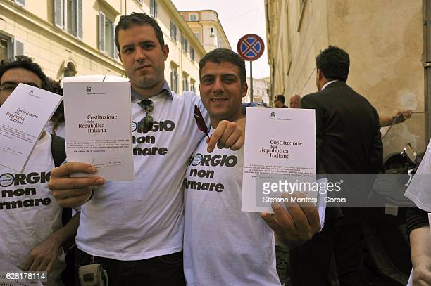Protestors hold out the Italian Constitution during the demonstration of the Party Italy of Values outside the Quirinal Palace to ask the President...