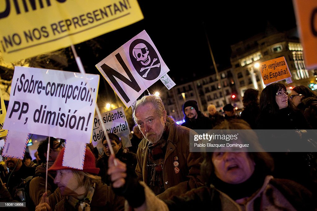 Protestors hold placards as they gather during a demonstration against alleged corruption scandals implicating the PP (Popular Party), on the streets of Madrid on February 3, 2013 in Madrid, Spain. Spain's Prime Minister Mariano Rajoy yesterday denied receiving undeclared payments from his political party. More information on secret payments were revealed today and leader of opposition socialist Party (PSOE) urged Rajoy to resign.