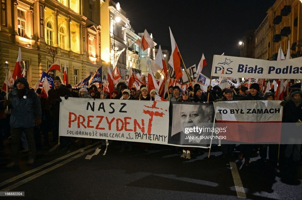 Protestors hold polish national flags and a banner with the portrait of late president Lech Kaczynski which reads 'This was a coup' referring to the...