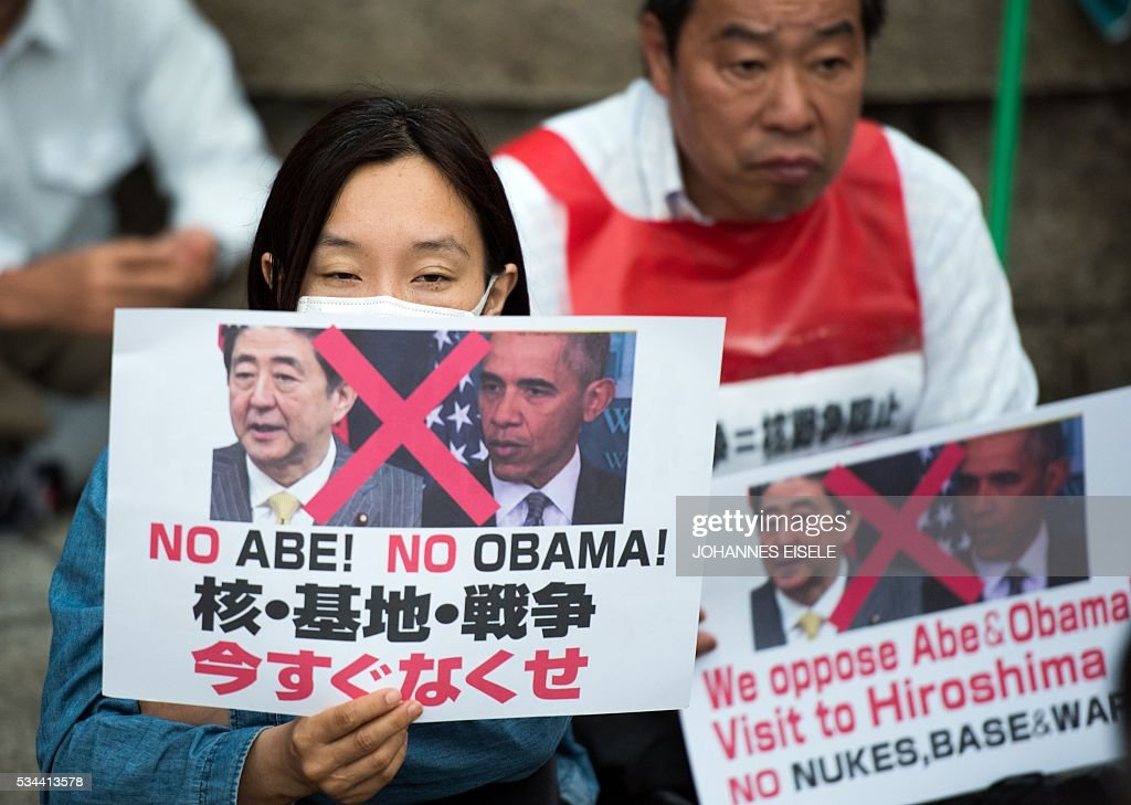 Protestors hold posters reading 'No Abe! No Obama - We oppose Abe and Obama visit to Hiroshima' during a demonstration next to the Hiroshima Peace Memorial park in Hiroshima on May 26, 2016. US President Barack Obama is set to become the first sitting US president to visit one of the bomb sites when he journeys on May 27, 2016 with Japanese Prime Minister Shinzo Abe to Hiroshima, hallowed ground to Japanese but, for more than 70 years, a no-go zone for 11 of his Oval Office predecessors. / AFP / JOHANNES