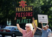 Protestors hold signs against fracking during a demonstration outside of the California Environmental Protection Agency headquarters on July 25 2012...