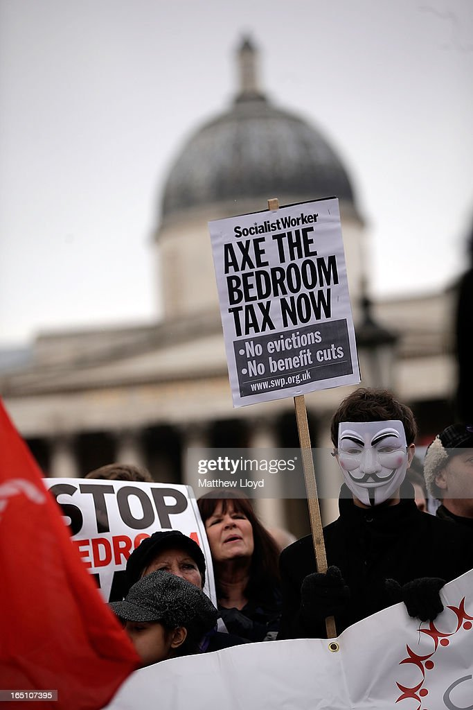 Protestors hold signs and wear masks as they demonstrate against the proposed 'bedroom tax' gather in Trafalgar Square before marching to Downing Street on March 30, 2013 in London, England. Welfare groups are protesting the government's plans to cut benefits where families have surpassed the number of rooms they require.