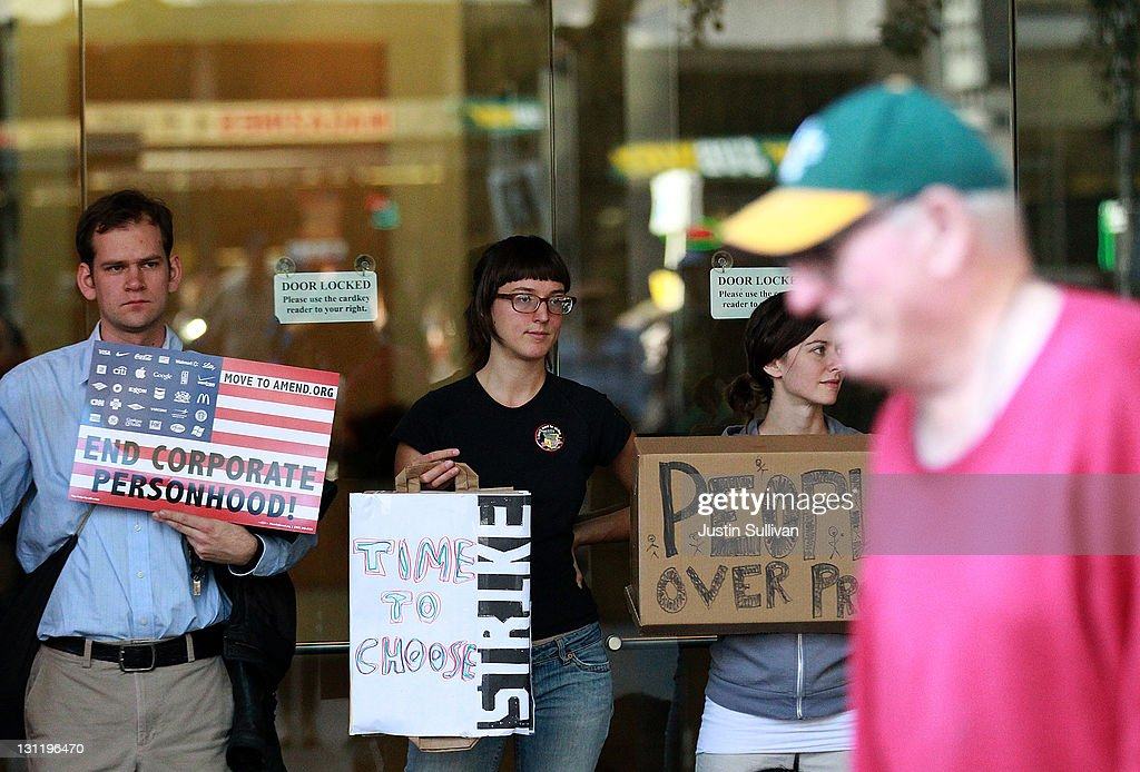 Protestors hold signs as they block the entrance to a CitiBank office during Occupy Oakland's general strike demonstration on November 2, 2011 in Oakland, California. Thousands of protestors have taken to the streets for a general strike organized by Occupy Oakland.