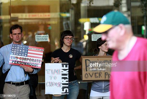 Protestors hold signs as they block the entrance to a CitiBank office during Occupy Oakland's general strike demonstration on November 2 2011 in...