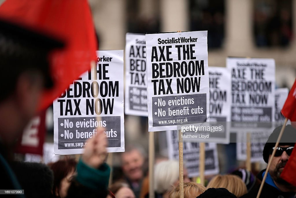 Protestors hold signs as they demonstrate against the proposed 'bedroom tax' gather in Trafalgar Square before marching to Downing Street on March 30, 2013 in London, England. Welfare groups are protesting the government's plans to cut benefits where families have surpassed the number of rooms they require.