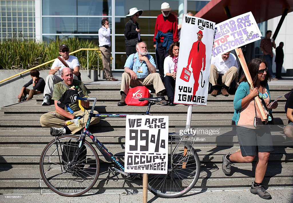 Protestors hold signs as they demonstrate outside of the W Hotel before the arrival of U.S. President Barack Obama on October 25, 2011 in San Francisco, California. Hundreds of protestors from a wide variety of activist groups staged protests outside of the W Hotel where President Obama was holding a $7,500 per person fundraiser.