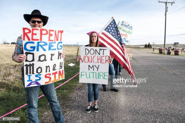 Protestors hold signs at a rally for Republican Greg Gianforte as he campaigns for the Montana House of Representatives seat vacated by the...