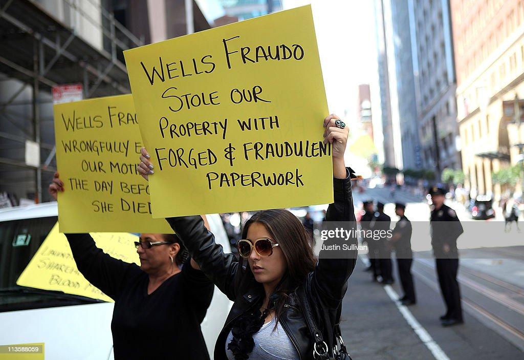 Protestors hold signs during a demonstration outside of the Wells Fargo shareholders meeting on May 3, 2011 in San Francisco, California. Over 100 housing activists staged a demonstration outside of the Wells Fargo shareholders meeting accusing the banking giant of predatory lending and foreclosing on homes by using fradulent paperwork.