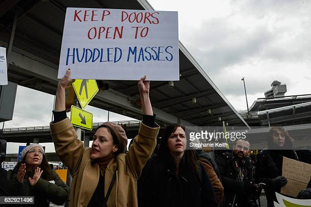 Protestors hold signs during a protest against the Muslim immigration ban at John F Kennedy International Airport on January 28 2017 in New York City...