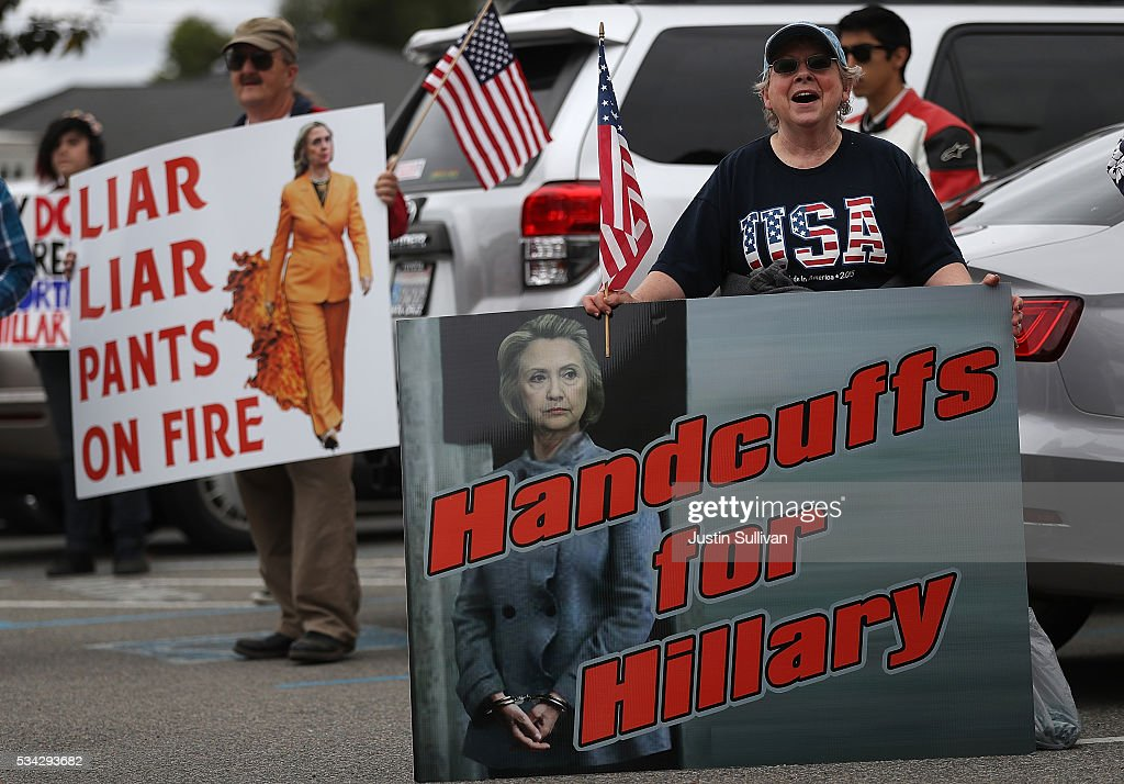 Protestors hold signs outside of a campaign rally for democratic presidential candidate former Secretary of State Hillary Clinton at Harrell College on May 25, 2016 in Riverside, California. Hillary Clinton is campaigning in California ahaed of the State's presidential primary on June 7th.