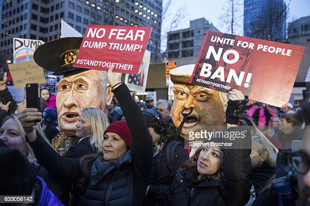 Protestors hold up signs in front of effigies of US President Donald Trump and Russian President Vladimir Putin during in a demonstration on January...