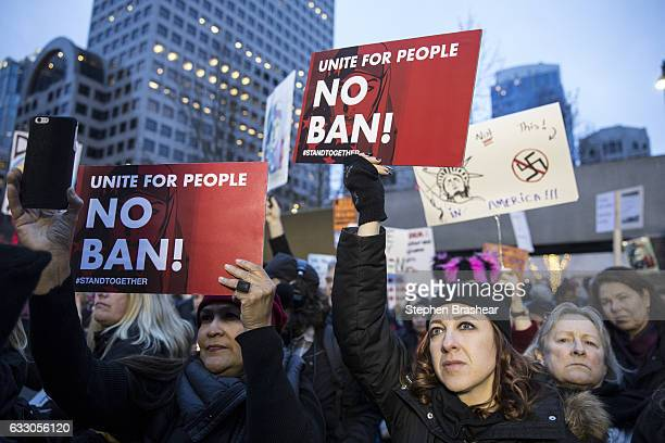 Protestors hold up signs while taking part in a demonstration on January 29 2017 in Seattle Washington against US President Donald Trump's executive...