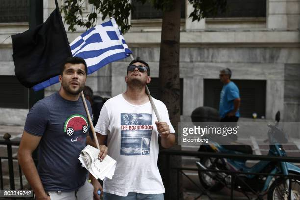 Protestors holding a Greek national flag and a black flag look on during a demonstration by municipal contract workers in Athens Greece on Thursday...