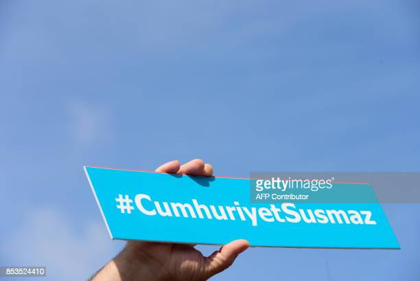 A protestors holds a sign with the hashtag 'Cumhuriyet will not be silent' during a demonstration in front of Istanbul's court house on September 25...