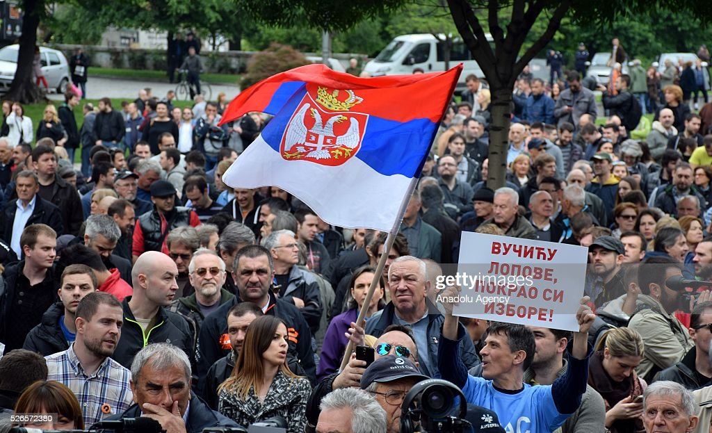 Protestors holds banner and wave Serbian flag in front of the Electoral Commission during a protest organised by Serbian main opposition parties against alleged electoral 'fraud' at last weekend polls in downtown Belgrade, Serbia on April 30, 2016.