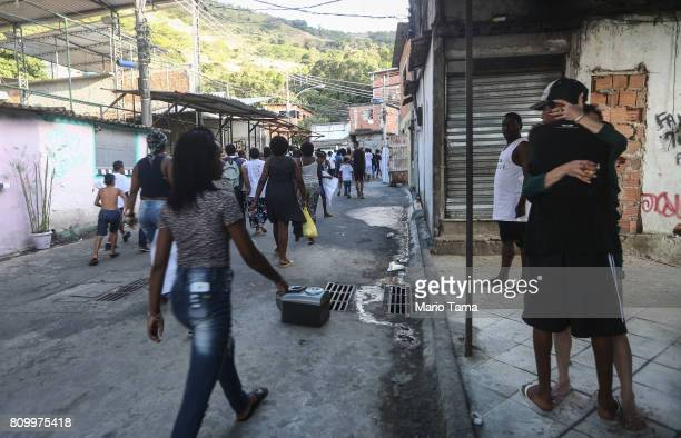 Protestors hug as others march through the Lins favela community following the funeral of Vanessa dos Santos who was shot in the head and killed in...