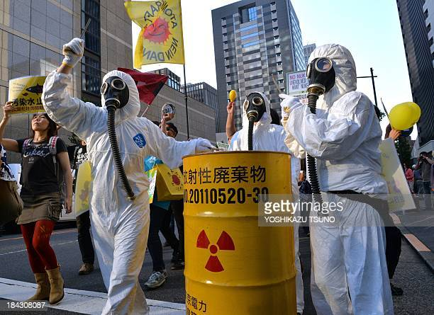 Protestors in radiation protection suits bang a drum can during an anti nuclear demonstration in front of the headquarters of the Tokyo Electric...