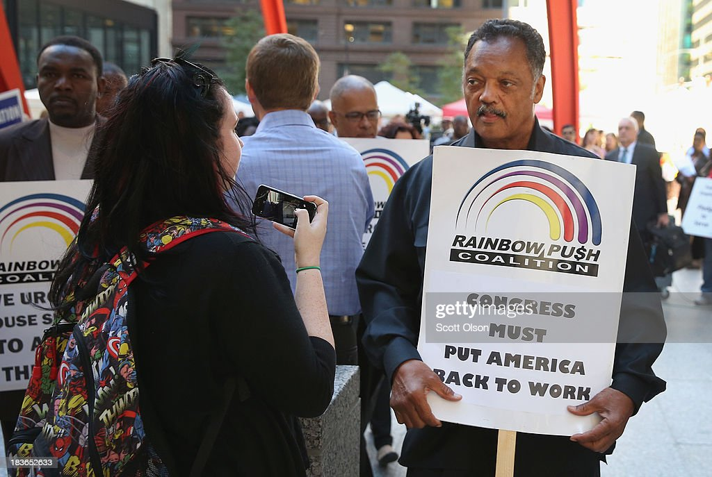 Protestors join Rev. Jesse Jackson (2nd R) during a march to call for an end to the federal government shutdown on October 8, 2013 in Chicago, Illinois. The protest was organized by the Rev. Jesse Jackson and the Rainbow PUSH Coalition as well as local labor, faith and community leaders.