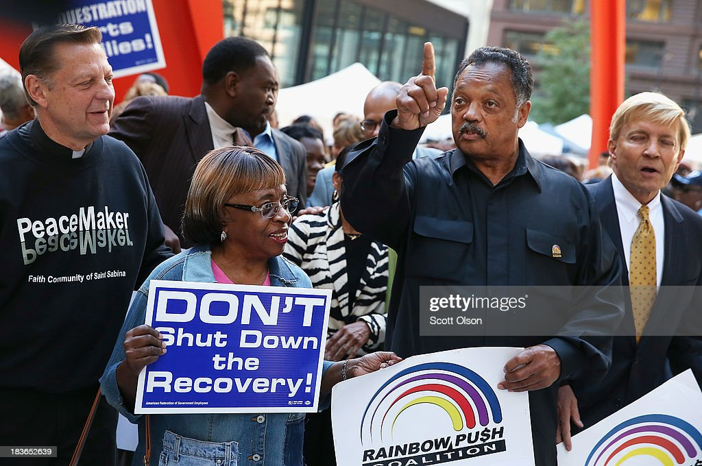 Protestors join Rev. Jesse Jackson (2nd from Right) during a march to call for an end to the federal government shutdown on October 8, 2013 in Chicago, Illinois. The protest was organized by the Rev. Jesse Jackson and the Rainbow PUSH Coalition as well as local labor, faith and community leaders.