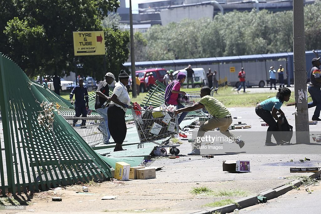 Protestors make a getaway with their loot on January 21, 2013, in Sasolburg, South Africa. Residents started to protest following the proposed incorporation of several towns into Sasolburg Municipality.