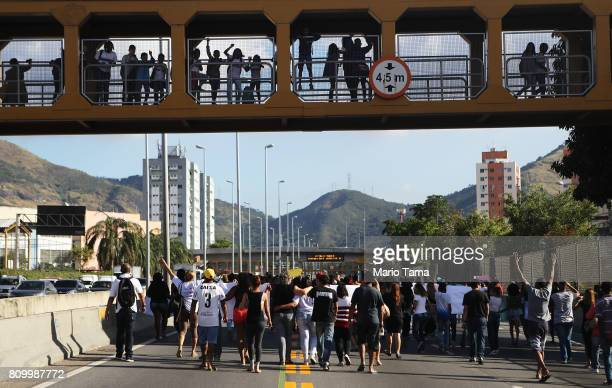 Protestors march along a highway following the funeral of Vanessa dos Santos who was shot in the head and killed in the doorway of her house during a...