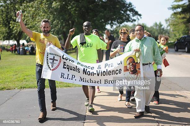 Protestors march and display signs during a peaceful rally in Ferguson Missouri on August 23 2014 as the community prepares to rebuild and heal after...
