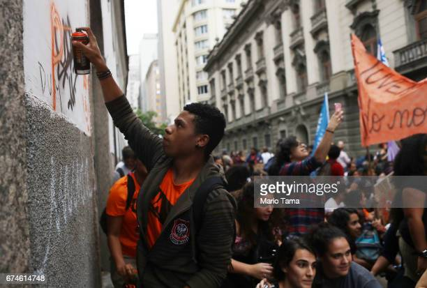 Protestors march as a man spray paints at a demonstration during a nationwide general strike on April 28 2017 in Rio de Janeiro Brazil The general...