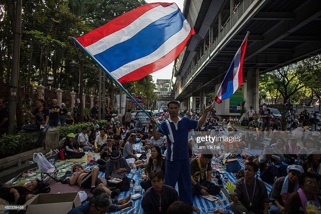 Protestors occupy the main road outside the police headquarter on November 28, 2013 in Bangkok, Thailand. Thailand's embattled Prime Minister Yingluck Shinawatra, survived a parliamentary no-confidence vote today but has failed to defuse anti-government protests. Unarmed anti-government demonstrators have managed to shut down a number of government offices over the past few days.