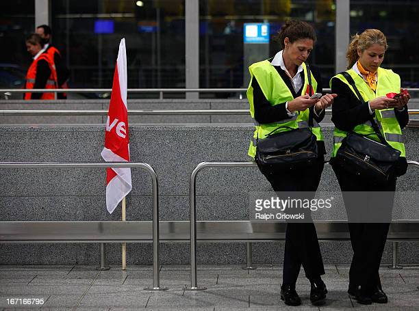 Protestors of Lufthansa ground service and maintenance personnel check their mobile phones during a nationwide protest at Frankfurt Airport on April...