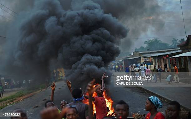 Protestors opposed to the Burundian president Pierre Nkurunziza's third term in office gather by a burning barricade during a demonstration in the...