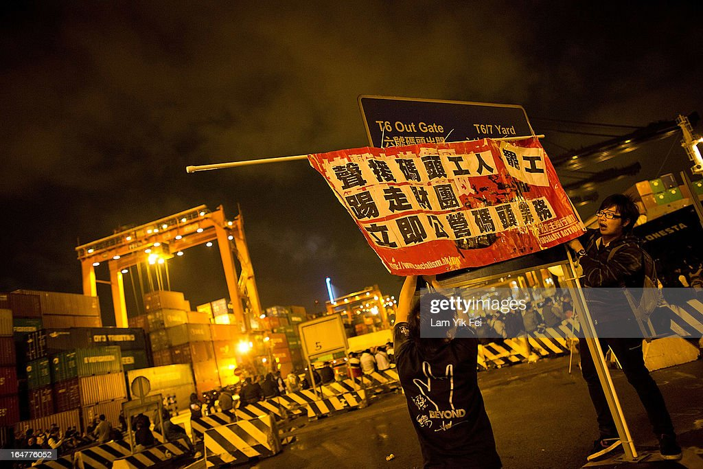 Protestors place a banner over a sign as over 100 dock workers stage a sit-in as they go on strike over pay at the Kwai Chung Container Terminal on March 28, 2013 in Hong Kong, China. The workers, who are employed by the Hongkong International Terminals, are demanding higher wages, claiming that they have not received a pay rise for 15 years.