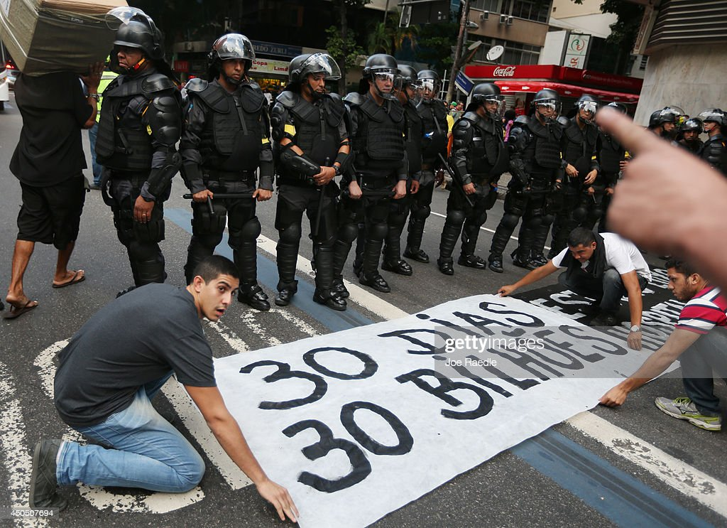 Protestors place a sign in front of police during an anti-World Cup demonstration in the Copacabana section on June 12, 2014 in Rio de Janeiro, Brazil. This is the first day of World Cup play.