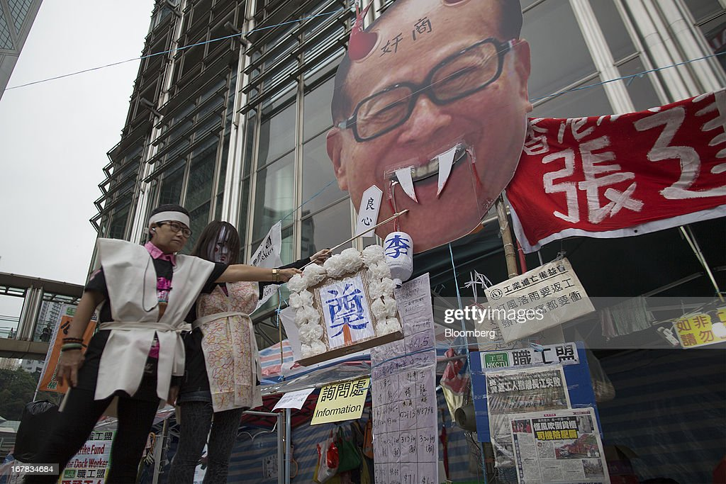 Protestors play a skit featuring an effigy of billionaire Li Ka-shing, chairman of Hutchison Whampoa Ltd. and Cheung Kong (Holdings) Ltd., in front of the Cheung Kong Center during a Labor Day march in Hong Kong, China, on Wednesday, May 1, 2013. Thousands of Hong Kong residents took to the streets today for Labor Day marches to petition for better labor conditions and in support of strike action by workers at docks operated by Li. Photographer: Jerome Favre/Bloomberg via Getty Images