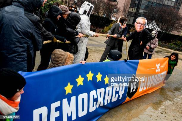 Protestors pose with cutouts of EU leaders and banners as they take part in a demonstration in front of the EU headquarters in Brussels on November...