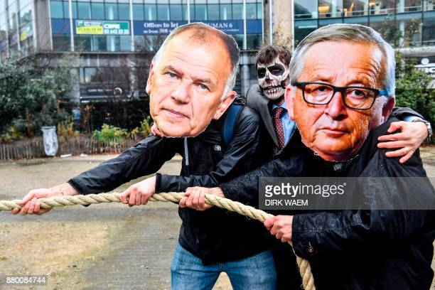 Protestors pose with cutouts of EU leaders as they take part in a demonstration in front of the EU headquarters in Brussels on November 27 against...