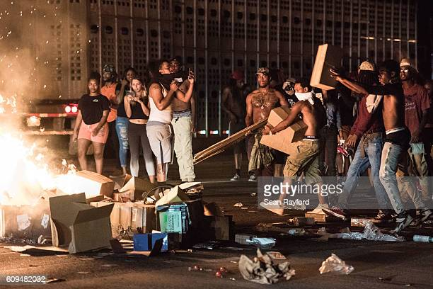 Protestors put cargo from tractor trailers onto a fire on I85 during protests in the early hours of September 21 2016 in Charlotte North Carolina The...