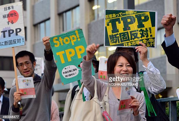 Protestors raise their fists and chant slogans during a rally against the Trans Pacific Partnership trade deal in front of the prime minister's...